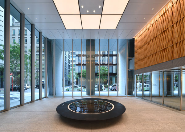 "Takeda Global Headquarters in Nihonbashi, Tokyo, Japan. In the 1st floor entrance space, a large circular stone filled with flowing water and light symbolizes ""the source of life"", and wooden artwork made of three-dimensional kanji motifs for ""water"" and ""light"" lines the walls."