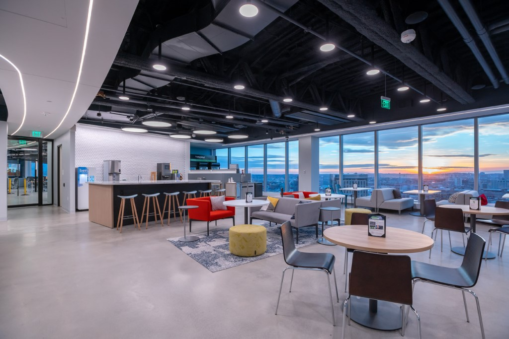 """On the top floor of PTC's new global headquarters, a large collaborative space called """"The Common"""" provides a variety of seating for both employees and customers. A large, open stair with a glass head-house connects The Common to the landscaped roof deck with outdoor seating. Photo credit: Warren Patterson Photography"""