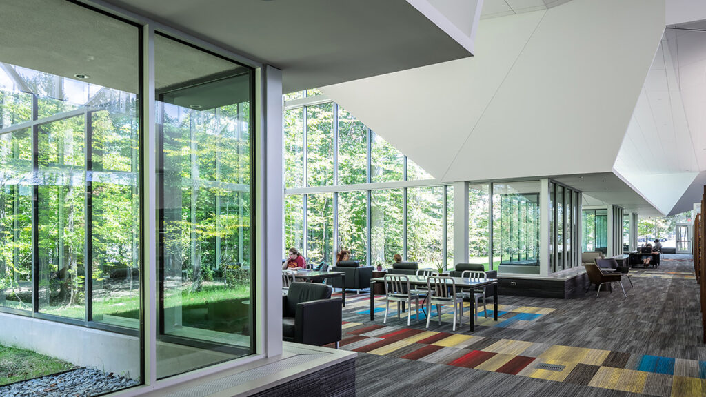 """The library experience continues outside thanks to an exterior reading room, and large spans of glass offer inspiring views of the light-dappled site,"" according to the description on the AIA/ALA Library Building Awards website. Photo credit: © Brandon Stengel"