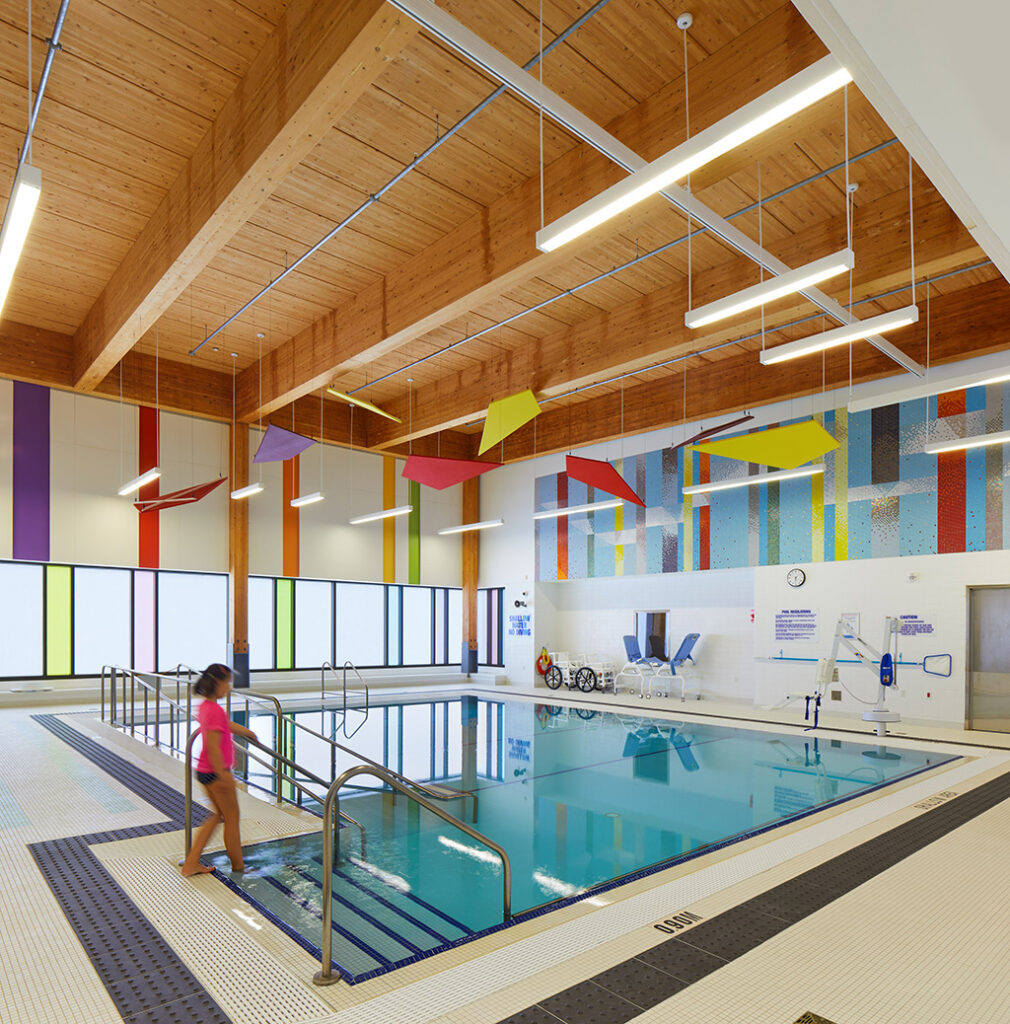 This image shows the colorful kites that function as sound baffling for the pool area at ErinoakKids' Brampton location. Courtesy of Stantec