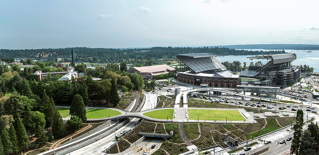 View of the Pedestrian Land Bridge looking toward the new light rail station, Husky Stadium, and Lake Washington. The project set up a campus-scaled, legacy 'bone structure' for a place serving as the nexus of many transportation modes. ASLA 2019 Award of Excellence in General Design, University of Washington's Lower Rainier Vista Project / GGN / Photo by GGN